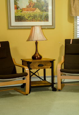 modern bedroom seating area in honey and brown with two brown chairs, table, and lamp