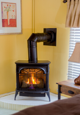 modern bedroom corner fire lit franklin stove honey colored walls and black stovepipe