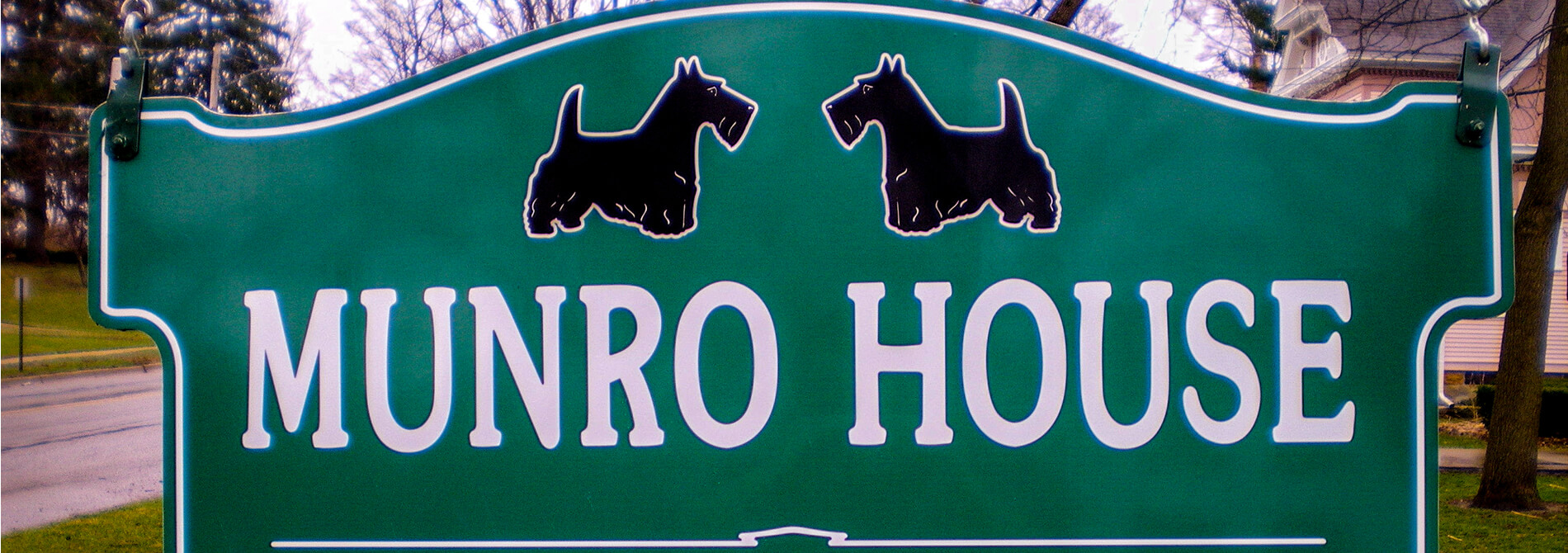 munro house green business sign with white lettering and two black scottish terrier dogs
