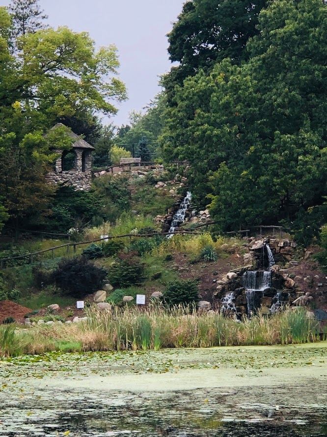 stone shelter on a hill with 2 waterfalls leading to a pond