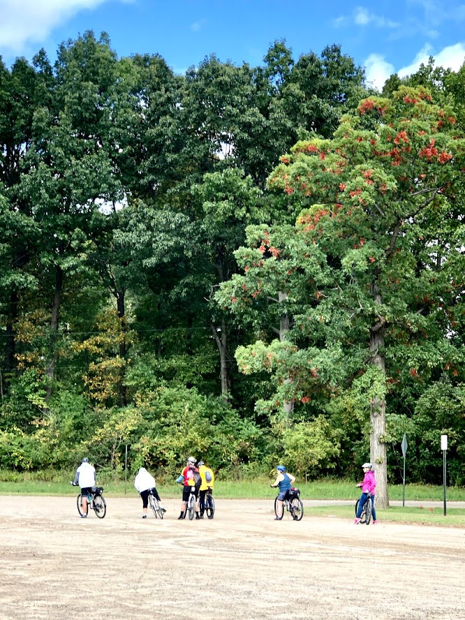 6 bike riders on a dirt path heading toward a forest of trees