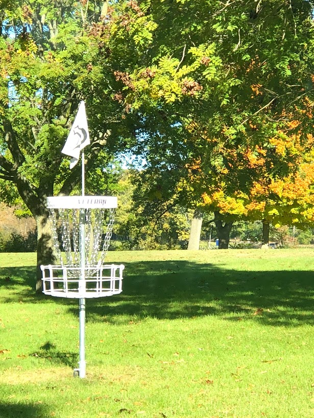 a white disc golf goal amidst green, yellow, and orange colored leaves during Fall colors season