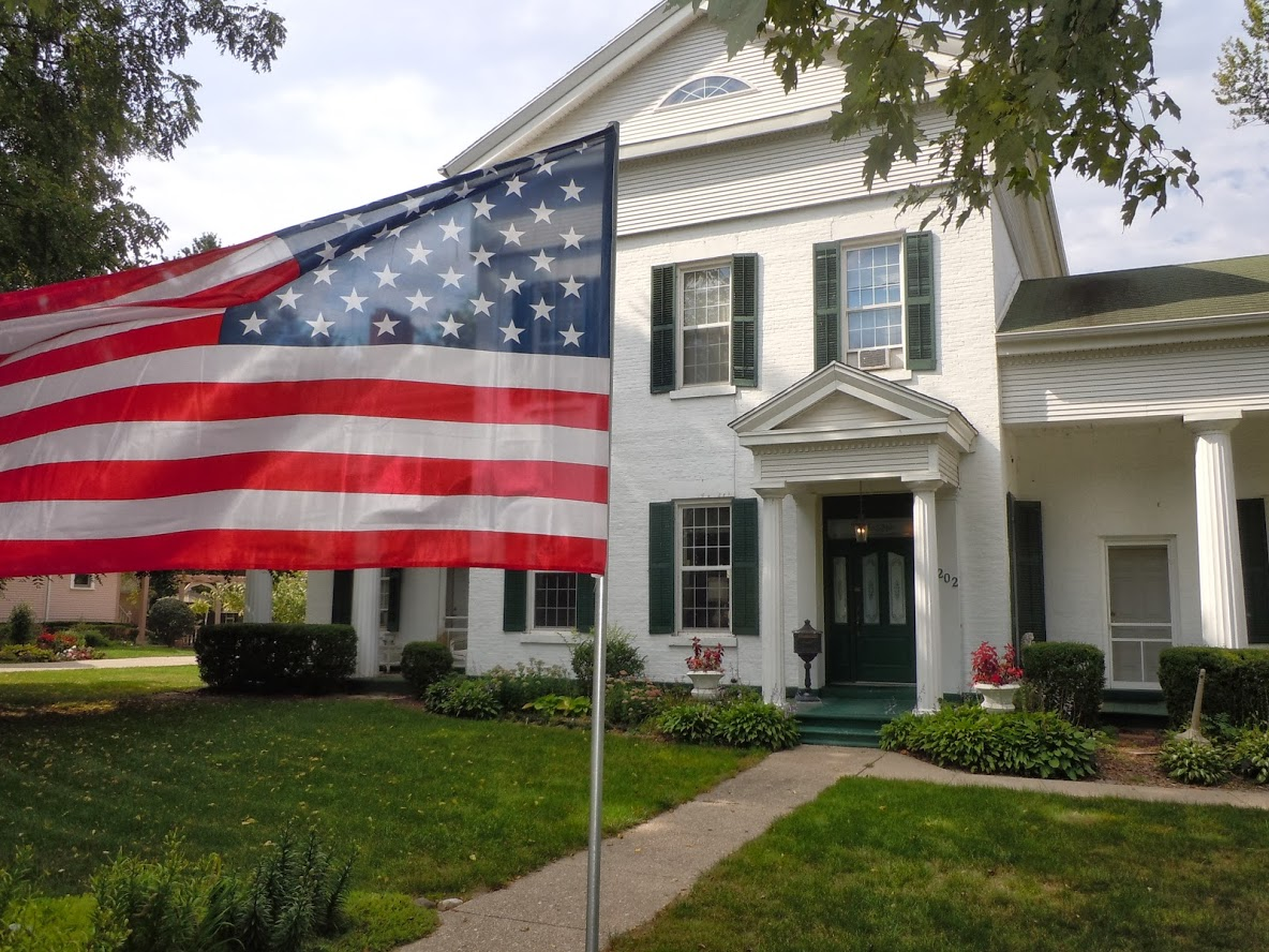 American Flag unfurled in front of white greek revival mansion