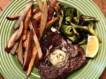Steak french fries and broccoli on a green ribbed plate with a slice of lemon