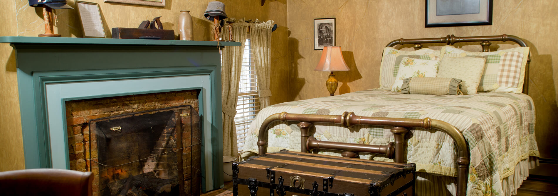 Historic civil war theme bedroom with cream walls striped travel chest brass framed bed