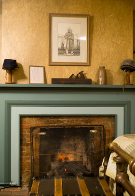 historic civil war theme bedroom fireplace with cream walls and blue/green façade