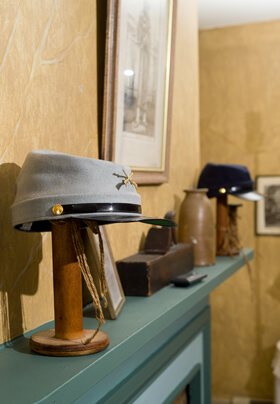 historic civil war theme bedroom gray confederate hat and blue union hat on blue/green mantel