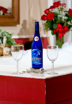 Blue wine bottle on the edge of maroon jacuzzi tub with red roses in background