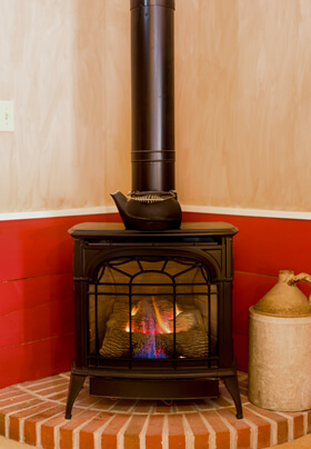 glass front lit franklin stove fireplace with black stovepipe on red brick step