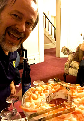 happy man in blue shirt serving shrimp cocktail in a home environment with wine colored carpet