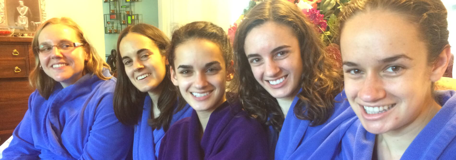 women in blue robes surrounding woman in purple robe at in-home spa day
