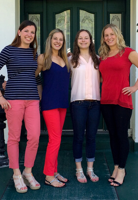 four young women posing in front of home with green doors and porch