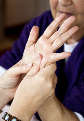 female cosmetologist with silver bracelet giving hand massage to older woman in purple robe