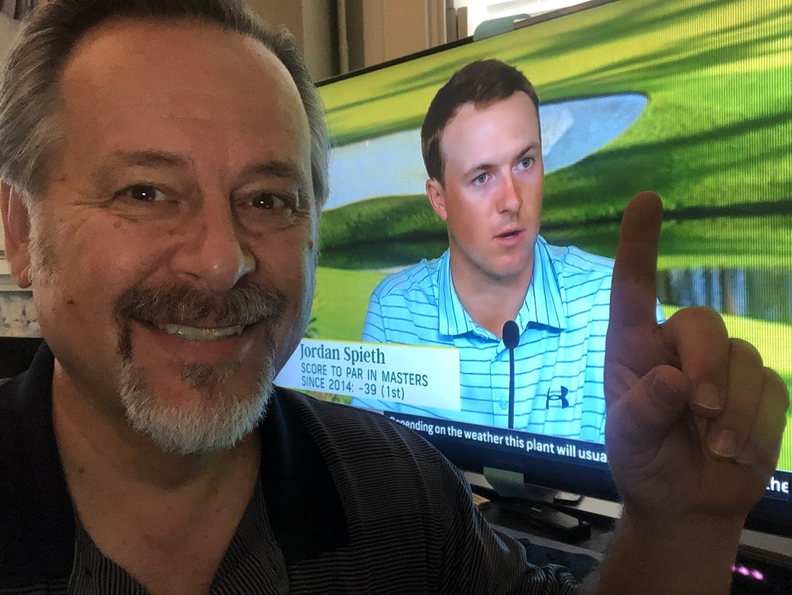 smiling man with finger pointed up in front of picture of professional golfer