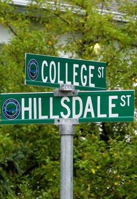 green street signs with white lettering corner of college street and hillsdale street