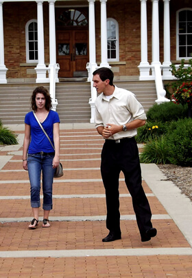 man in white shirt walking with woman in blue shirt in front of white pillared brick building