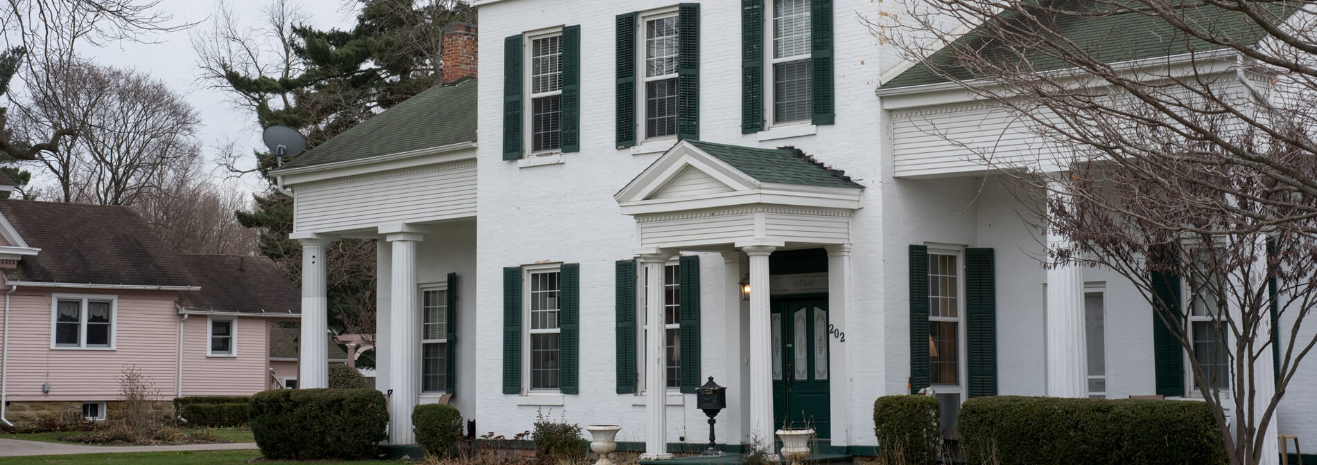 Historic White Greek Revival Style Munro House with Green Roof and Shutters