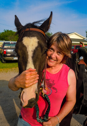 woman in pink halter top hugging white blazed brown horse