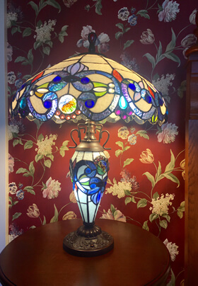 blue white and cream tiffany lamp on round wooden end table against red cream floral print wallpaper