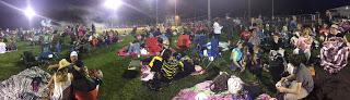 crowd gathering at dusk for fireworks in park