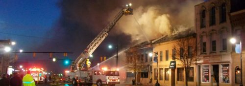 firefighter on ladder truck spraying water on burning building at night