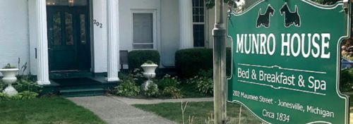 Green sign on front of white building