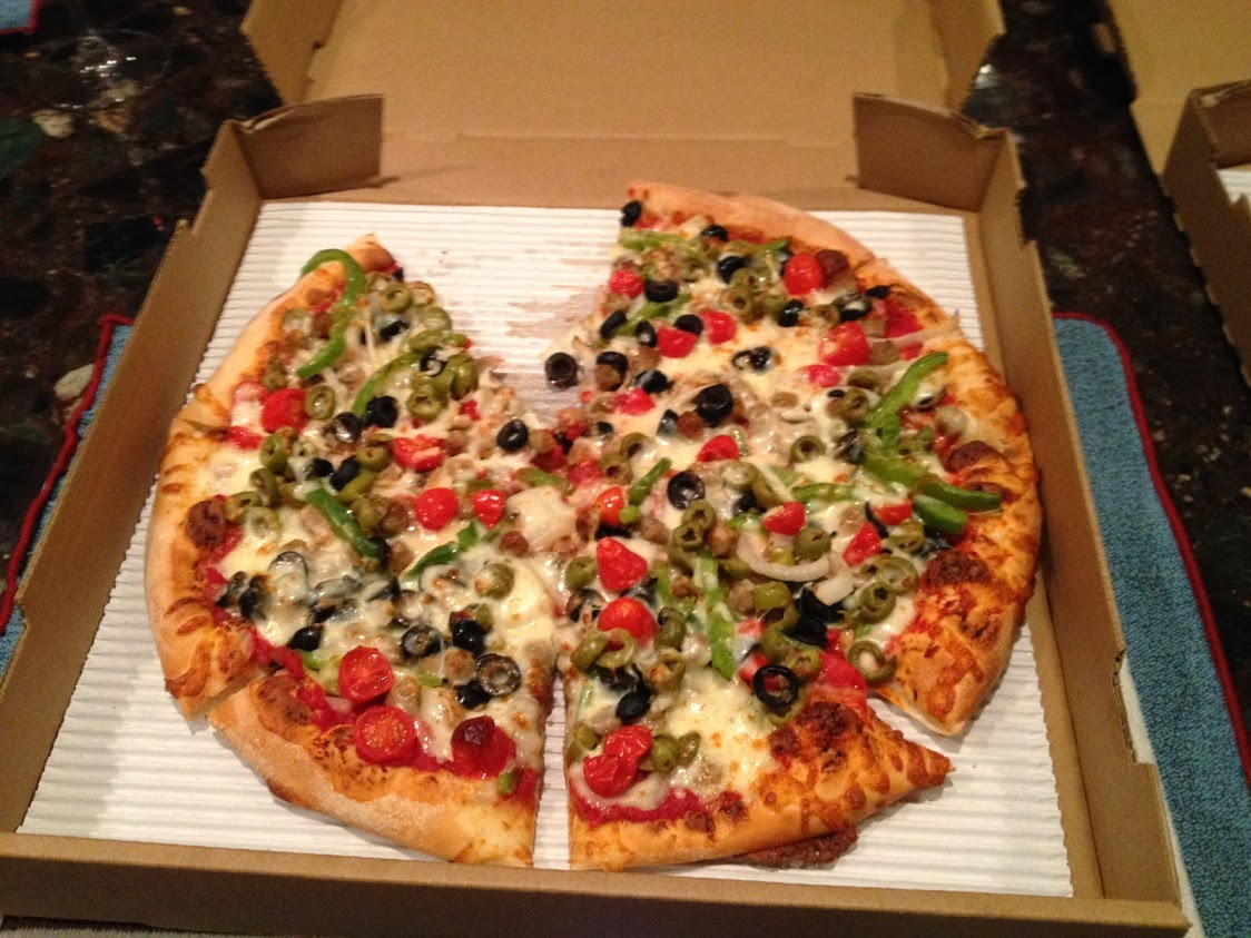 open pizza box with veggie pizza missing one slice