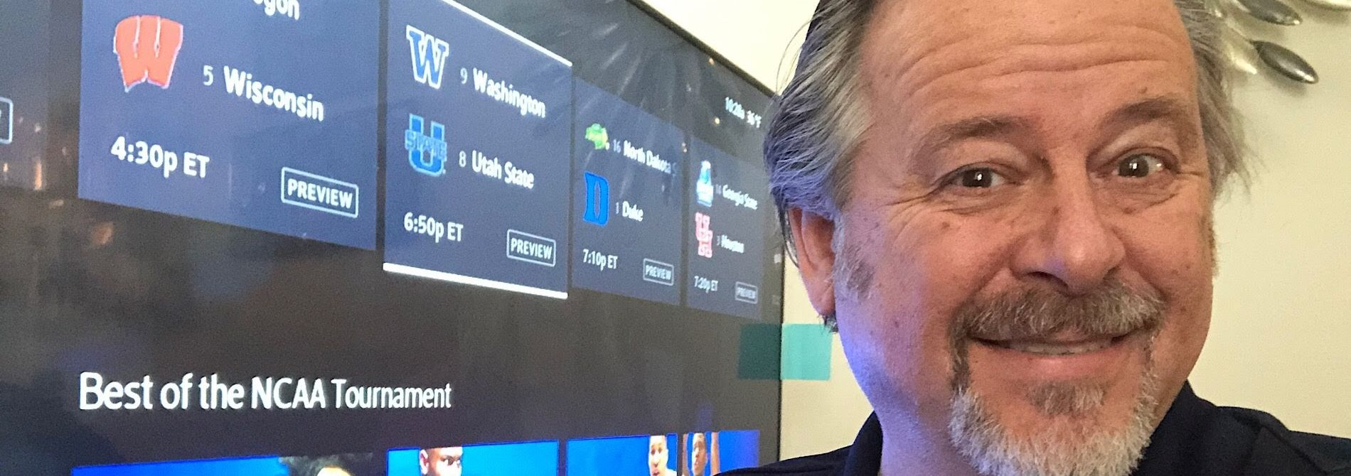 man in front of TV screen with ncaa basketball tournament choices