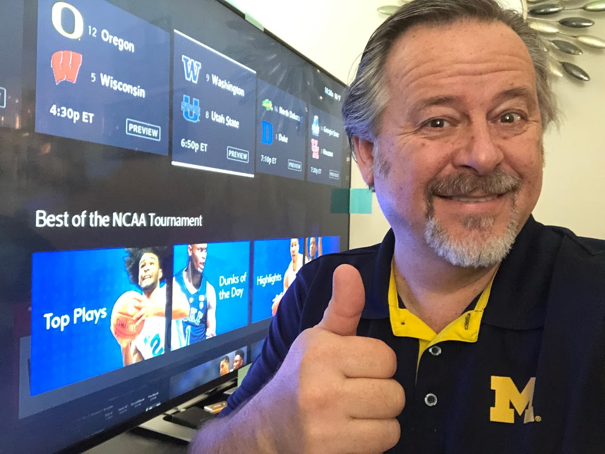 man with thumbs up near ncaa basketball tournament choices on cable tv