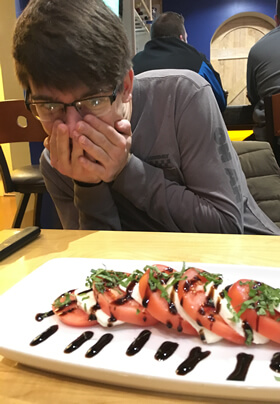 young man in gray shirt amazed by fancy capri salad with tomatoes cheese garnish and balsamic vinegar stripes