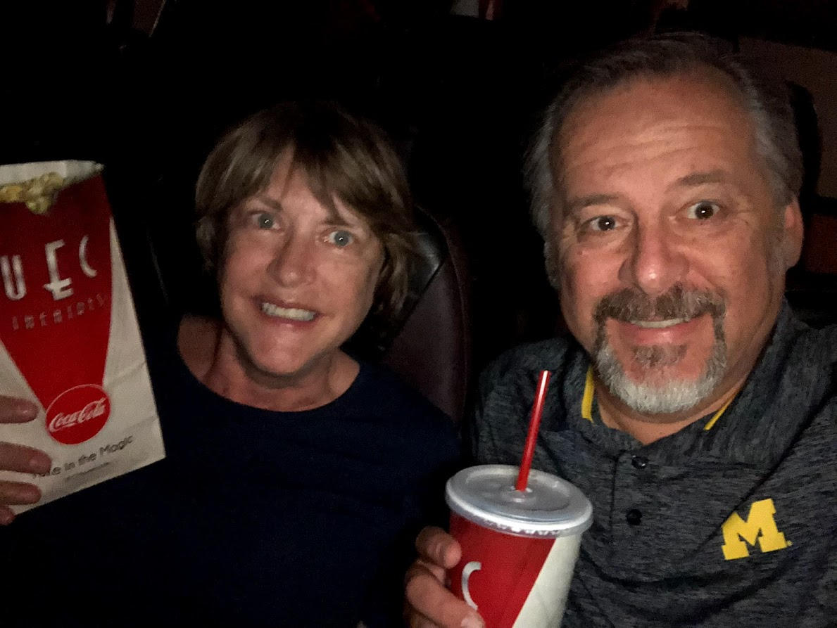 man and woman in a movie theater holding popcorn and beverage