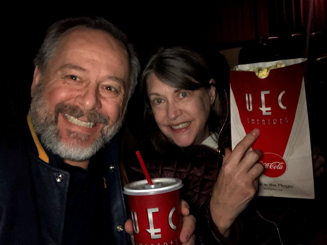 happy man and woman in darkened theater with pop and popcorn