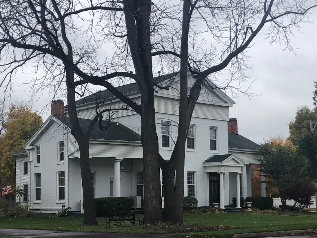 white greek revival home with large bare trees in the foreground and colorful trees is hues of green, yellow, and orange