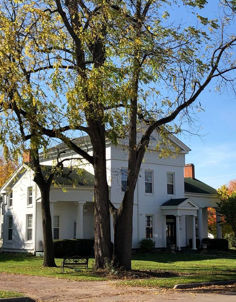 white greek revival style home in fall with fallen leaves from a black walnut tree in foregound