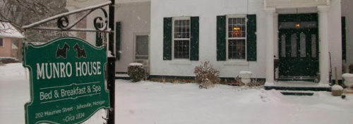 Green sign with white letters for Munro House B&B while snow falls around the white brick house