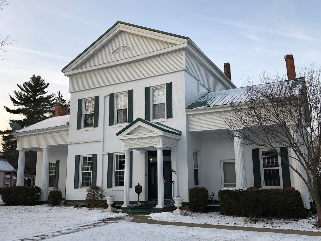 white house with green shutters and snow on the ground