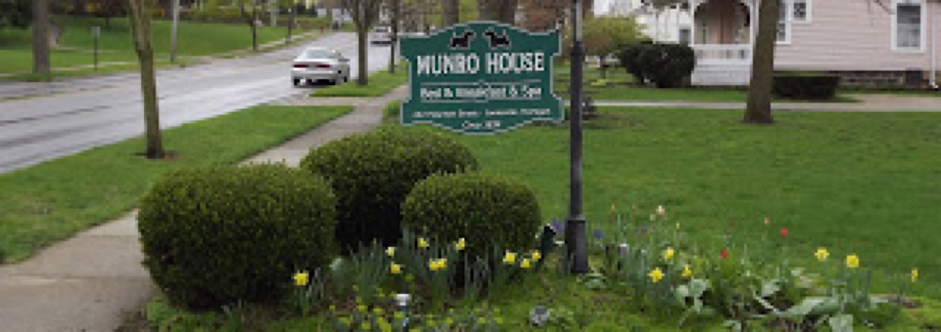 green and white munro house sign with yellow flowers