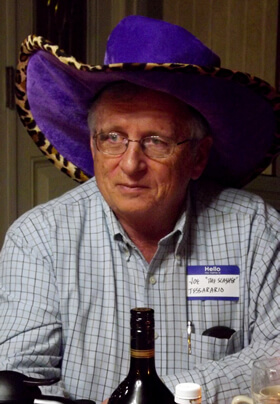man in blue checked shirt and purple pimp hat with name tag participating in murder mystery