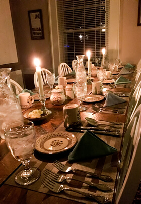dimly lit semi formal dinner table with candles silver ware and water glasses