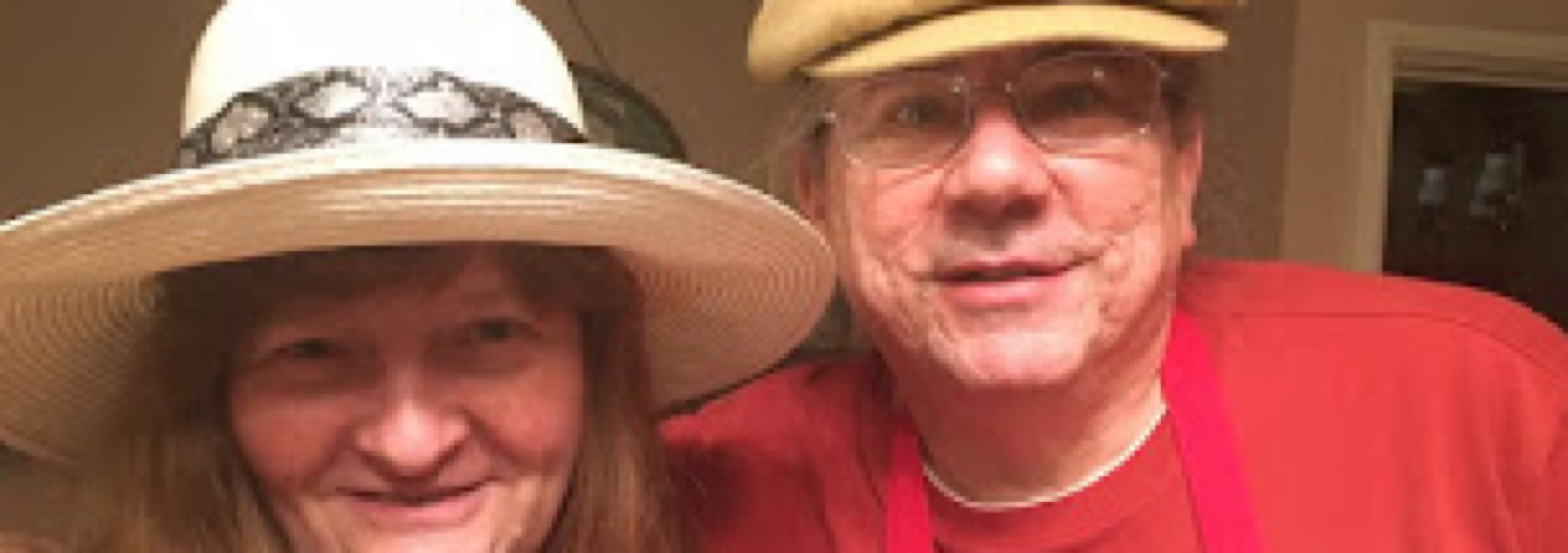 man in red shirt with woman in white hat