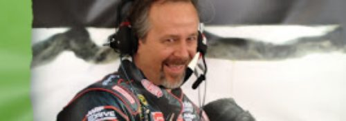 nascar man with headphones and sponsors uniform