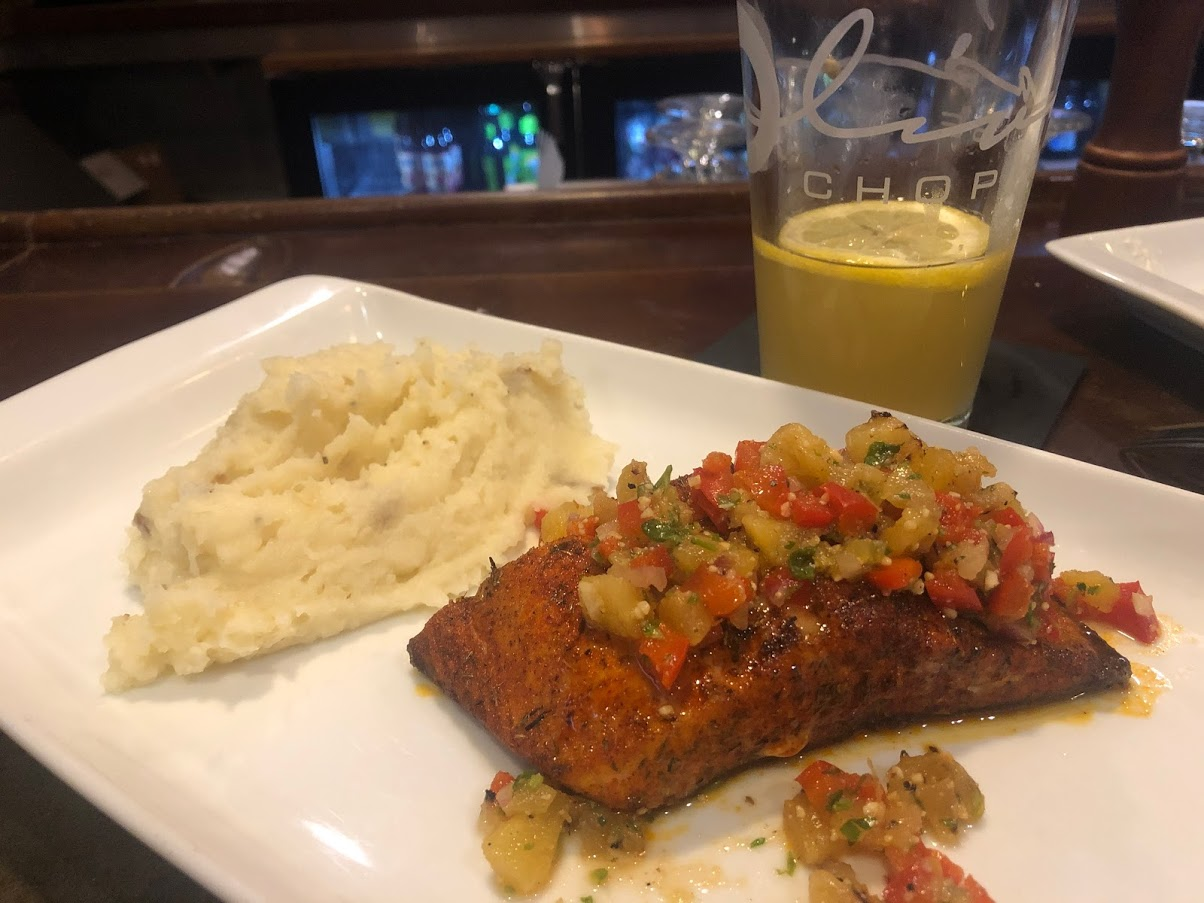 fried fish with vegetable salsa and mashed potatoes on a white plate and a half glass of beer