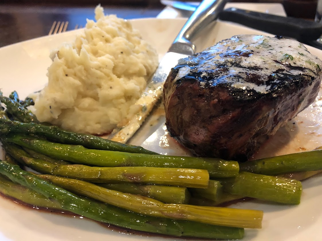 dinner plate with steak, green beans, and mashed potatoes