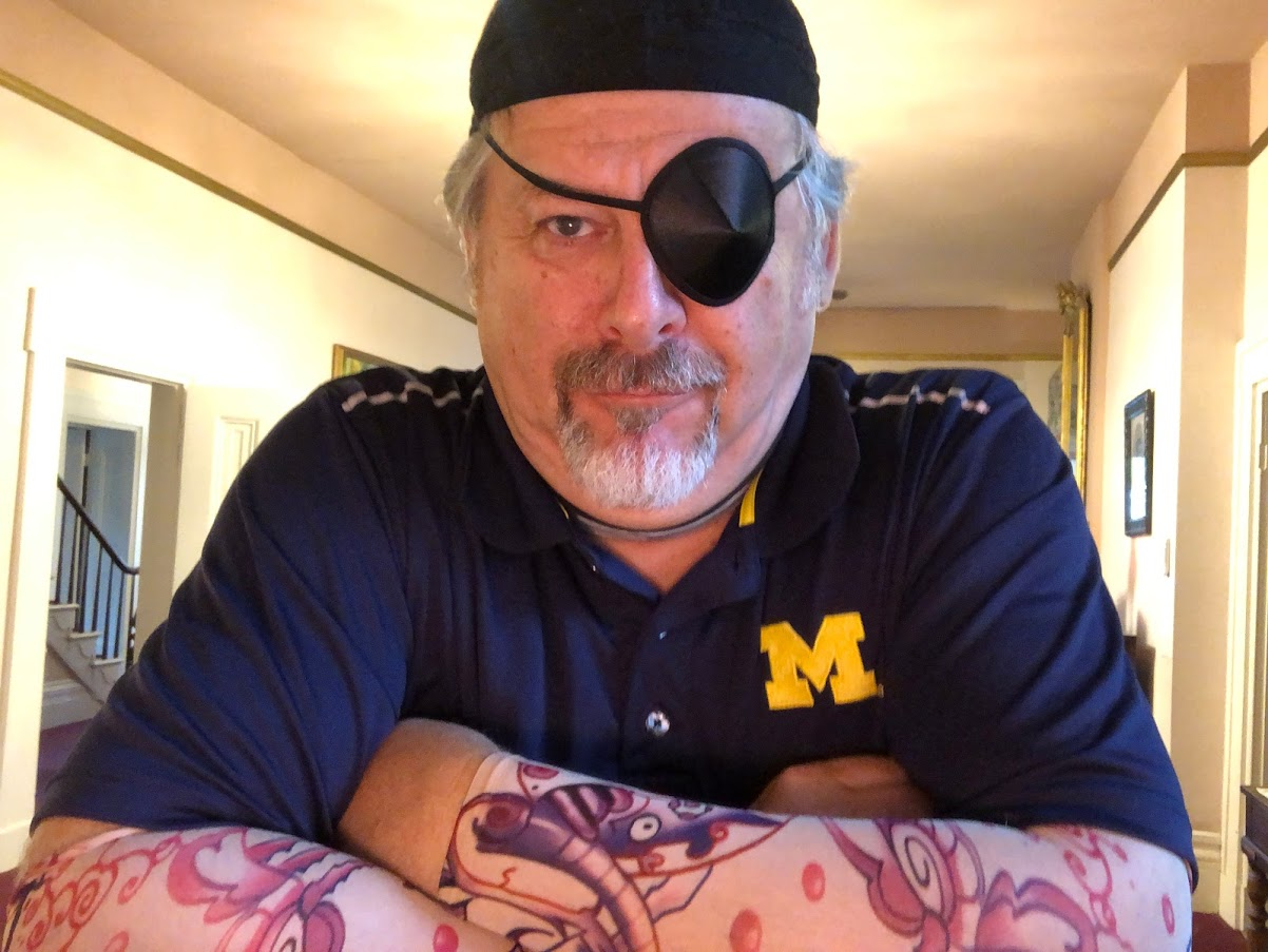 Man with a dew rag, eye patch, and tattoo sleeves looks like a pirate