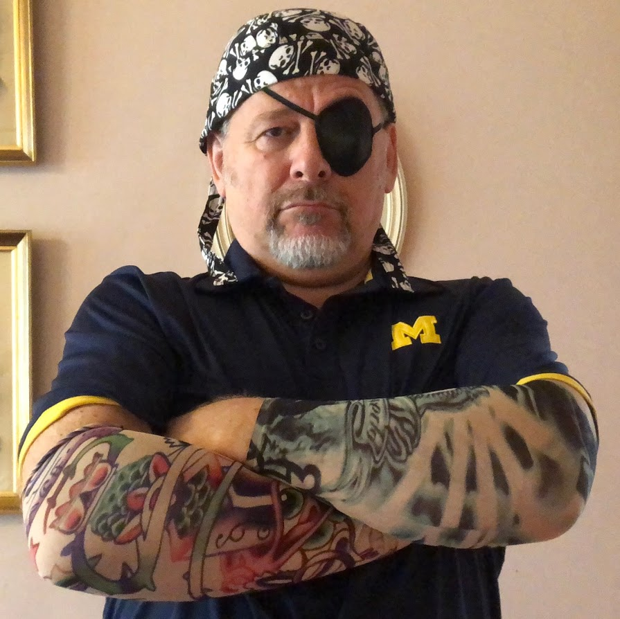 Goatee man wearing eye patch and skull & crossbones dew rag with multi colored tattoo sleeves on folded arms