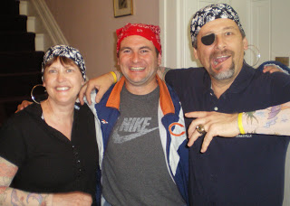 2 men and a woman dressed like pirates wearing dew rags and tattoo sleeves