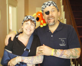 Man and woman with dew rags and tattoo sleeves with an orange dog perched on his shoulder