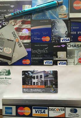 a variety of credit cards and a gift card used as payment options on an envelope with a green logo