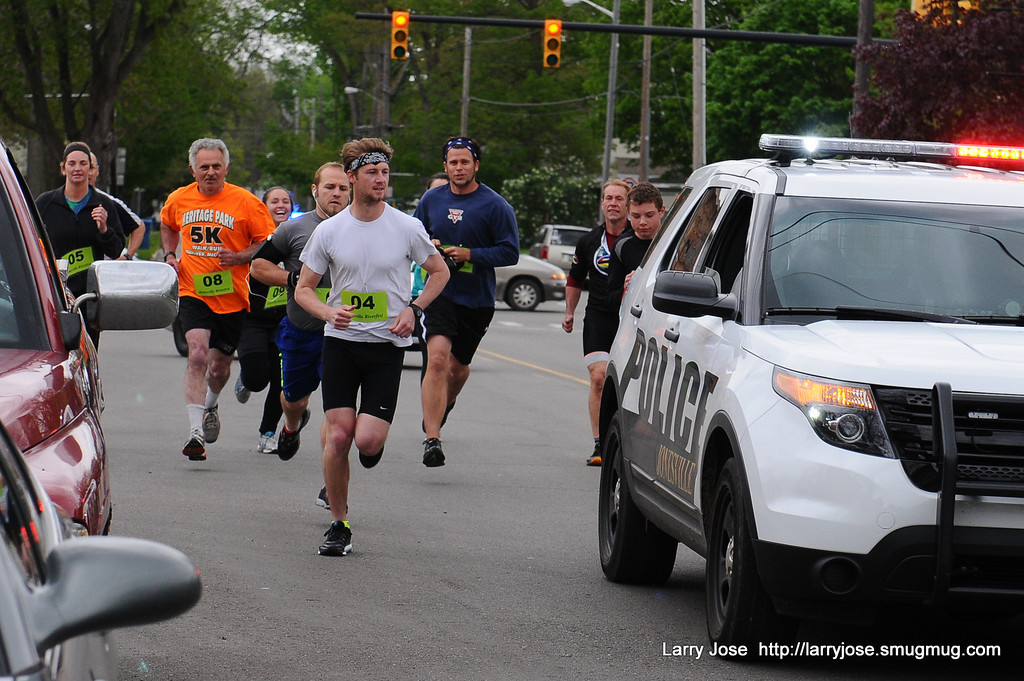 Road race runners escorted by police vehicle