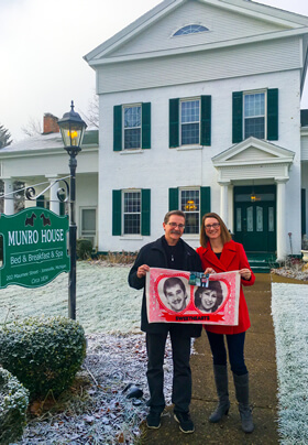 exterior of munro house in winter featuring man and woman holding red portrait mural near business sign
